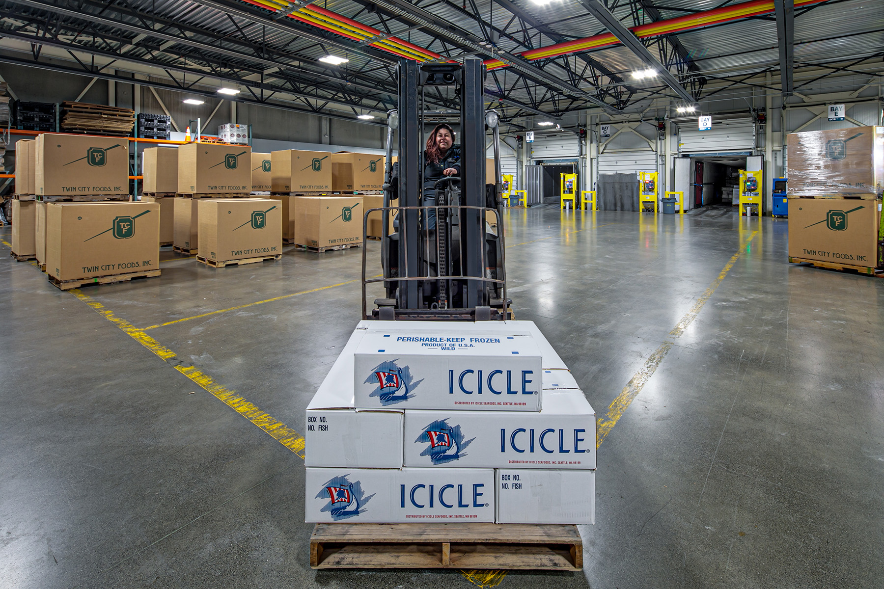 BCS worker driving a forklift loaded with a pallet of Icicle boxes.