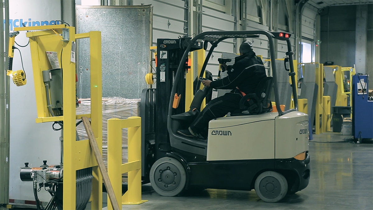 Worker driving forklift and using handheld scanner.