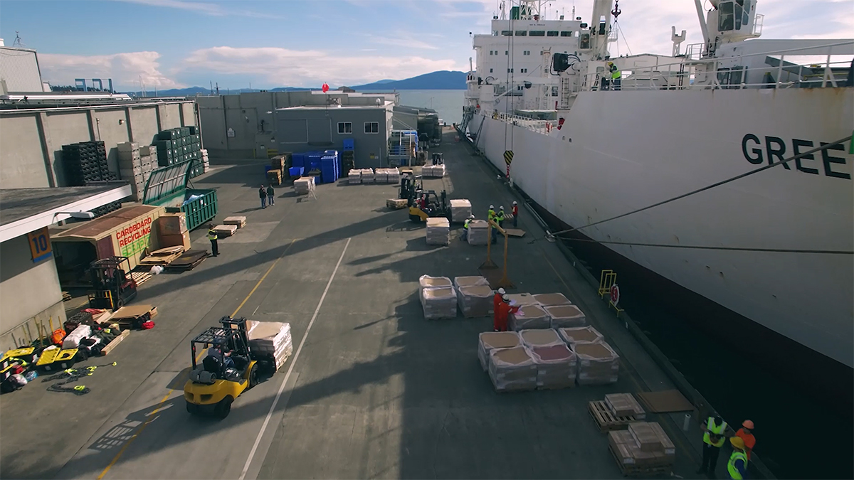 Overhead view of forklift driving down dock to load large ship.